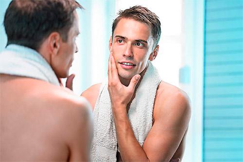 мужчина в ванной смотрит в зеркало